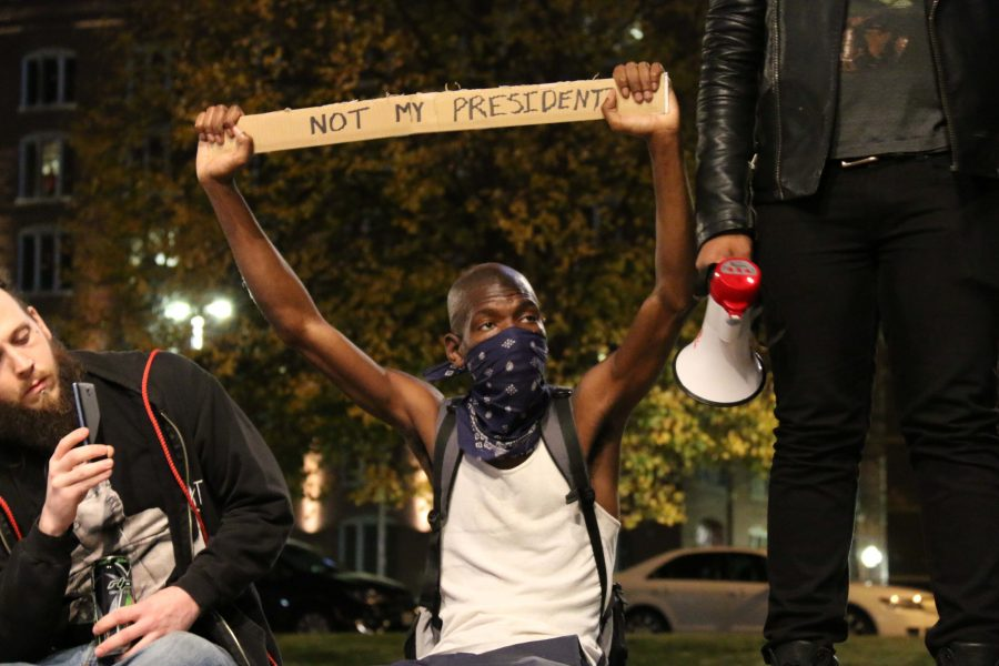 A masked man protests the highly anticipated election of now President Donald Trump on October 30, 2016.